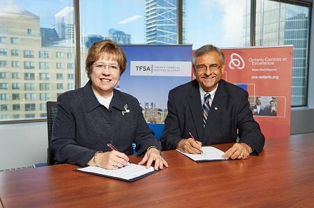 Janet Ecker, President and CEO of the Toronto Financial Services Alliance, and Dr. Tom Corr, President and CEO of Ontario Centres of Excellence, sign a new partnership agreement that will connect Toronto's financial services sector with Ontario's innovation ecosystem.