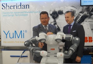 ABB Canada general manager Casey DiBattista and Sheridan College president Jeff Zabudsky (right) pose with YuMi, a small parts assembly robot that has been added to Sheridan's robotics lab. (CNW Group/Sheridan College).