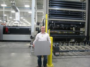 Laser cutting area with Steve Menegotto, general manager – datacom/electronic metal, holding cut metal enclosure materials at Hammond's Wilbert St. facility.