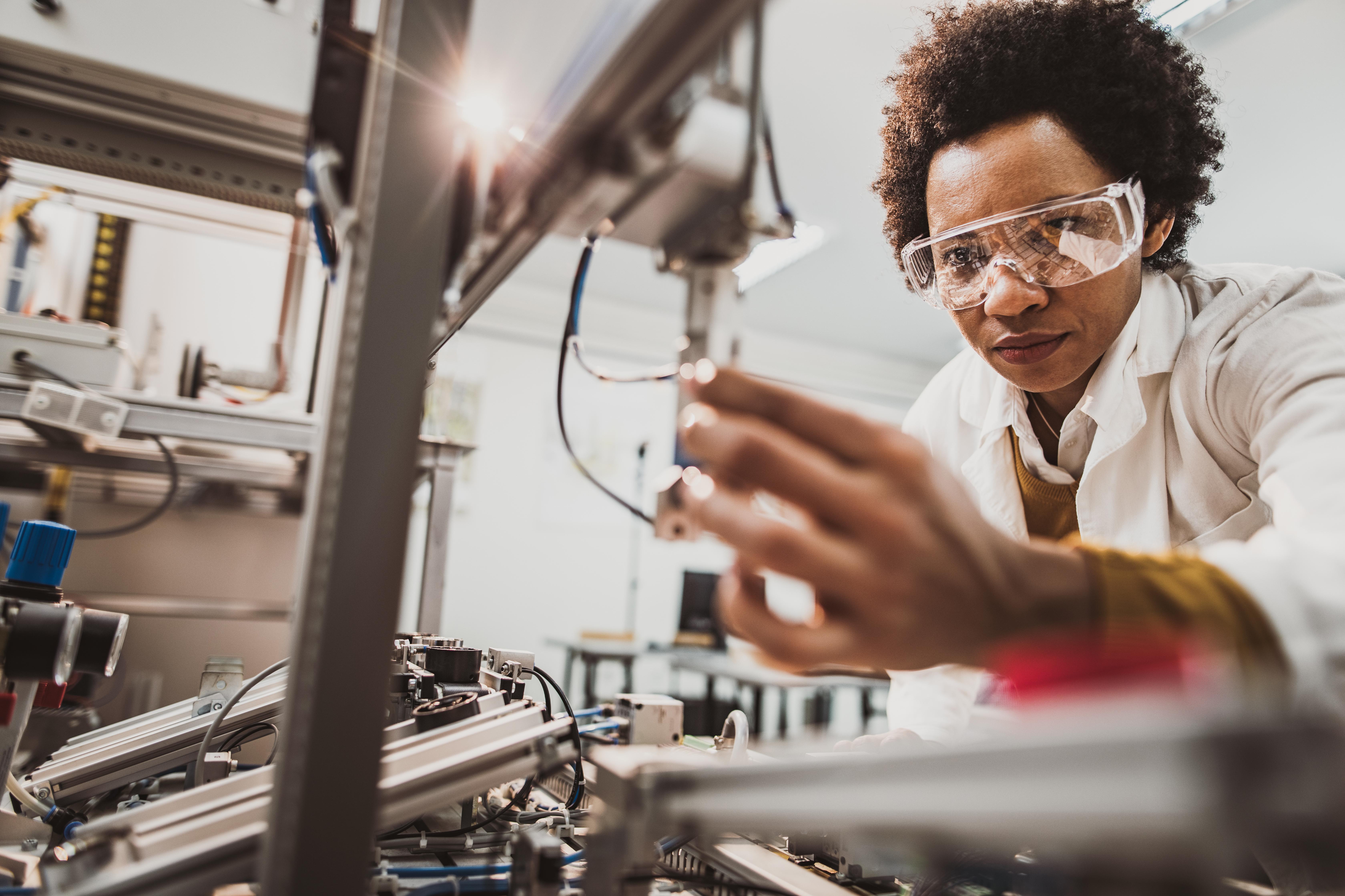 Black female engineer working on industrial machine in a laboratory.